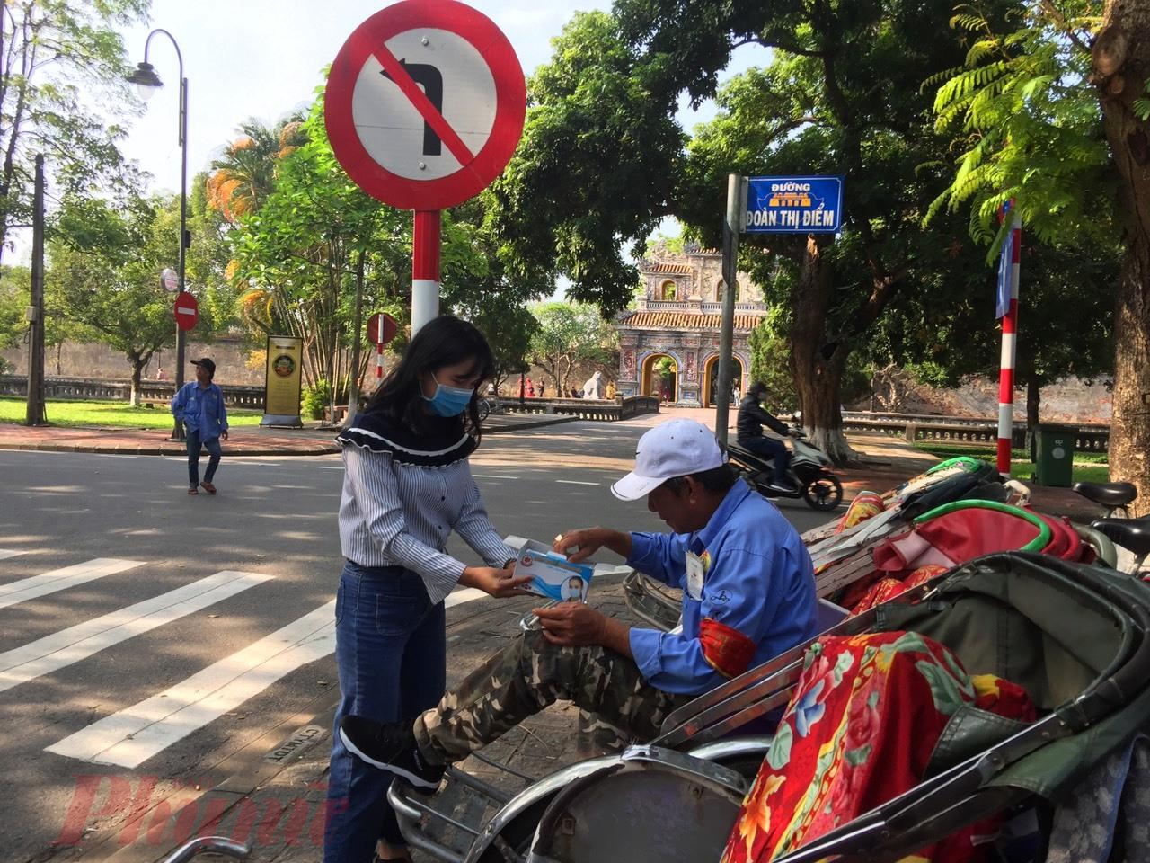 Từng khẩu trang y tế đã được chị Phạm Thị Diệu Huyền tận tình trao cho các bác tài xế xích lô Huế