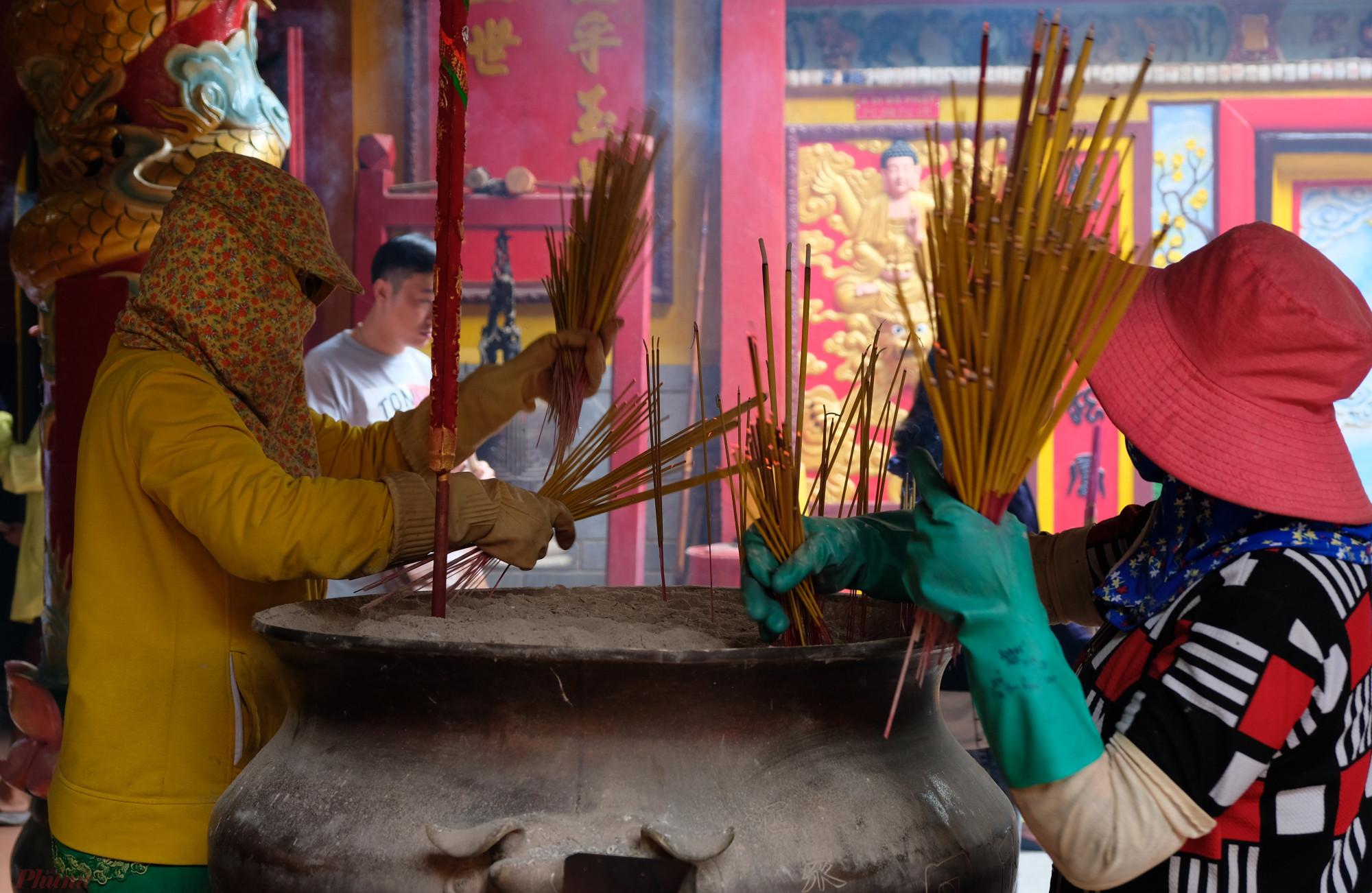 Số nhang thắp vào lư nhang ở Hội quán Ôn Lăng ngày mồng 6 Tết Nguyên đán 2020 nhiều đến nỗi, hai người rút đi mới kịp - Ảnh: Đậu Dung