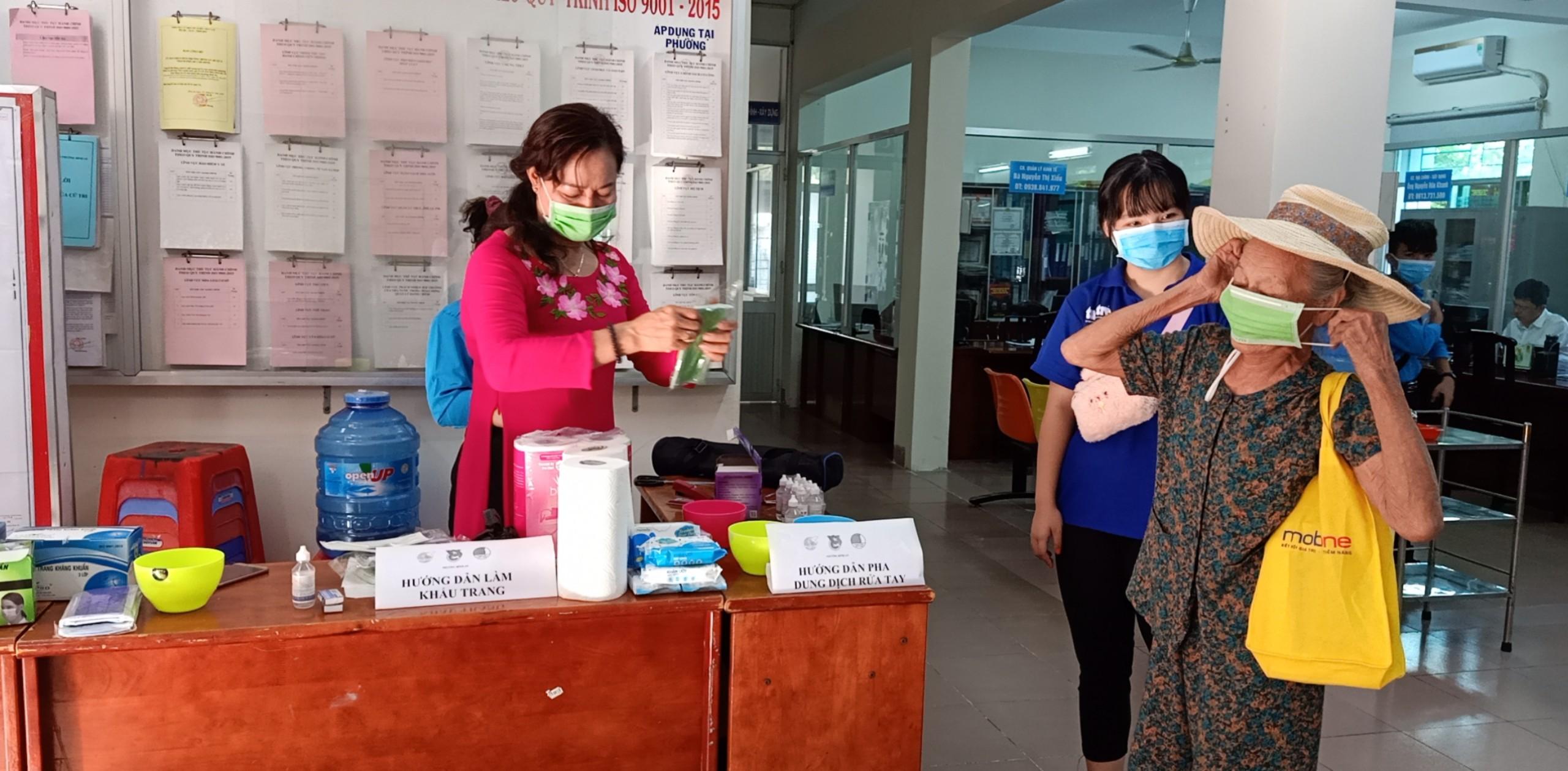 Cán bộ Hội ở phường Bình An, quận 2 tặng khẩu trang và hướng dẫn người dân pha dung dịch rửa tay.