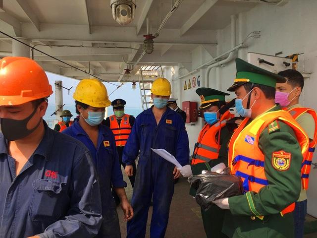 Lực lượng chức năng tiến hành kiểm tra thân nhiệt và phát khẩu trang miễn phí cho thuyền viên tàu Trung Quốc vừa cập cảng Gianh
