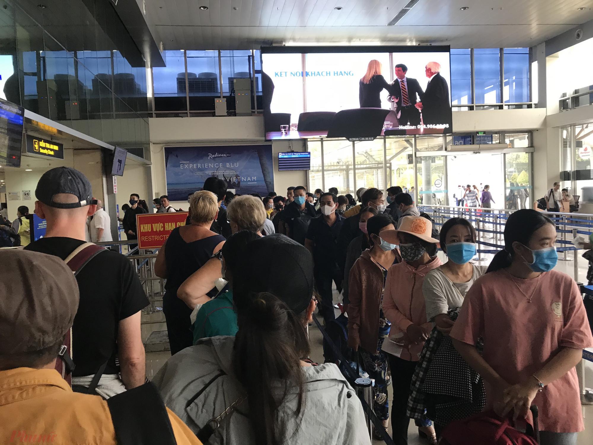 Khách hàng tại sân bay Tân Sơn Nhất bịt khẩu trang kín mít xếp hàng vào làm thủ tục hàng không. Ảnh: Quốc Thái
