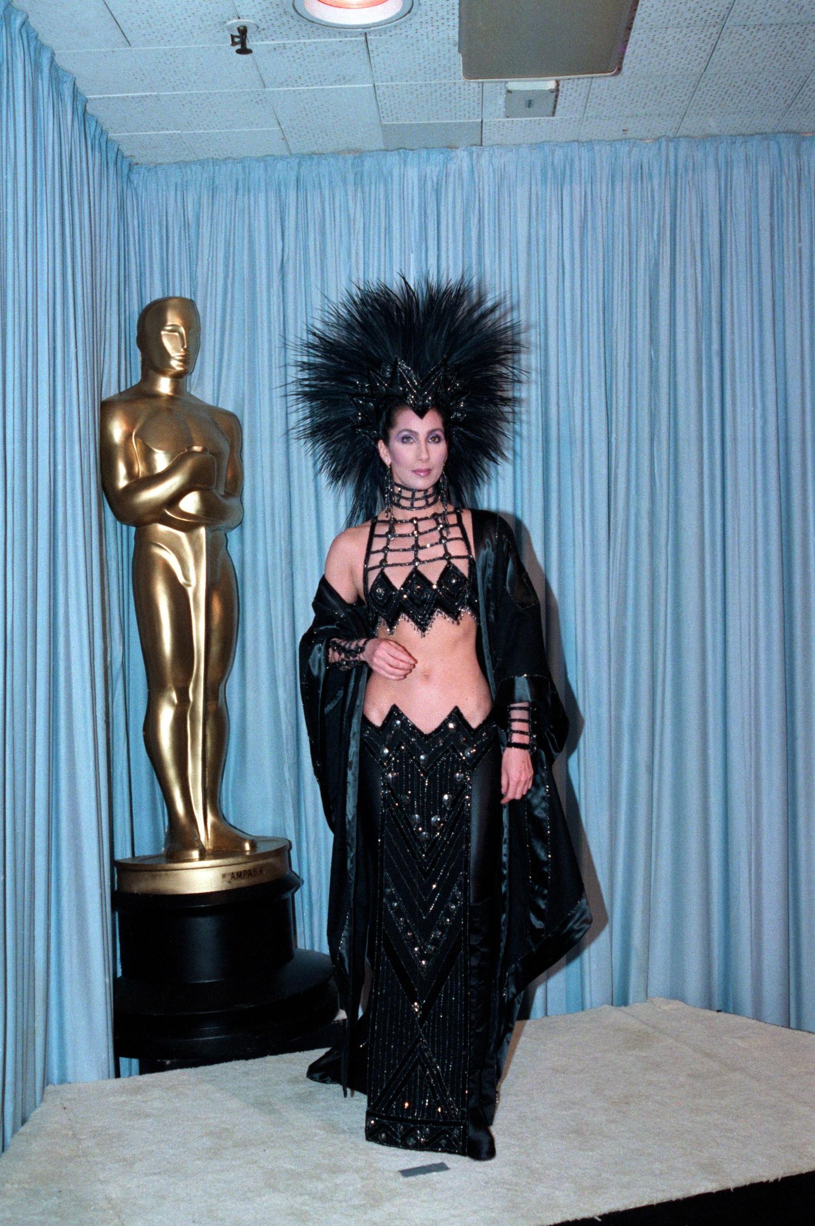 Cher, 1986 Cher, nữ hoàng sân khấu, chắc chắn đã đánh cắp thảm đỏ năm đó. Cô mặc một thiết kế của cộng tác viên lâu năm Bob Mackie: một chiếc váy đen đính sequin giữa lưng, hoàn chỉnh với một chiếc mũ lông đầy kịch tính. Đó là một diện mạo showgirl Las Vegas đầy đủ đã có người nói chuyện trong nhiều năm. Cô ấy đã mặc trang phục như một động thái thách thức chống lại Học viện, mà không thể đề cử cô ấy cho lượt của cô ấy trong Mặt nạ. Mặc dù Cher có thể hối tiếc sự lựa chọn, dù sao nó vẫn là biểu tượng. Tôi biết một số người trong Học viện đã không nghĩ rằng tôi là một nữ diễn viên nghiêm túc, cô ấy nói với tạp chí Vogue của Anh. Tôi luôn cảm thấy hơi buồn khi trao cho Don Ameche giải thưởng nam diễn viên phụ xuất sắc nhất trong bộ trang phục đó. Nó dường như làm anh hơi lo lắng.