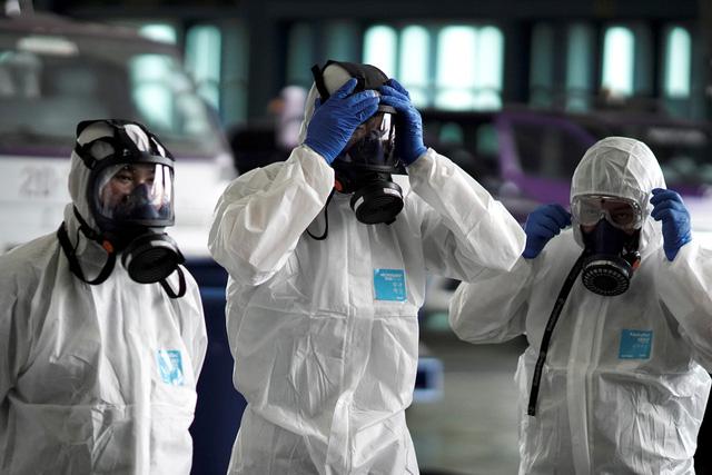Nhân viên y tế hỗ mặc đồ bảo hộ để điều trị cho người bệnh nhiễm virus corona.