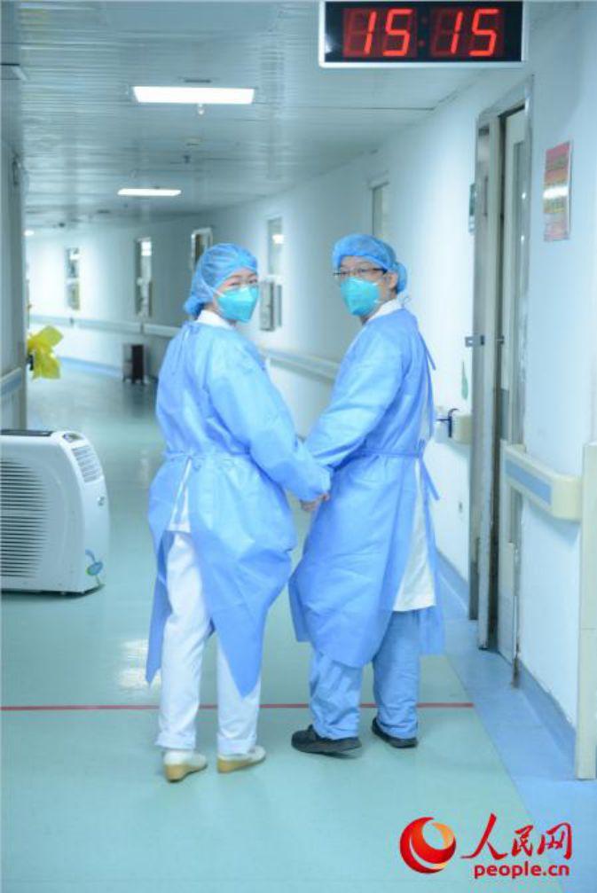 Nữ y tá Cao Shan nắm chặt tay chồng, bác sĩ Tu Shengjin. Cả hai đang tích cực cứu chữa cho các bệnh nhân nhiễm virus corona trong một bệnh viện ở Vũ Hán. Cặp đôi không dám về nhà do sợ lây nhiễm cho gia đình, họ tranh thủ chợp mắt tại văn phòng và trong xe hơi để tận dụng tối đa thời gian chăm sóc bệnh nhân. Không chỉ chăm sóc y tế, cả hai còn phải cho người bệnh lớn tuổi ăn và thay tã.