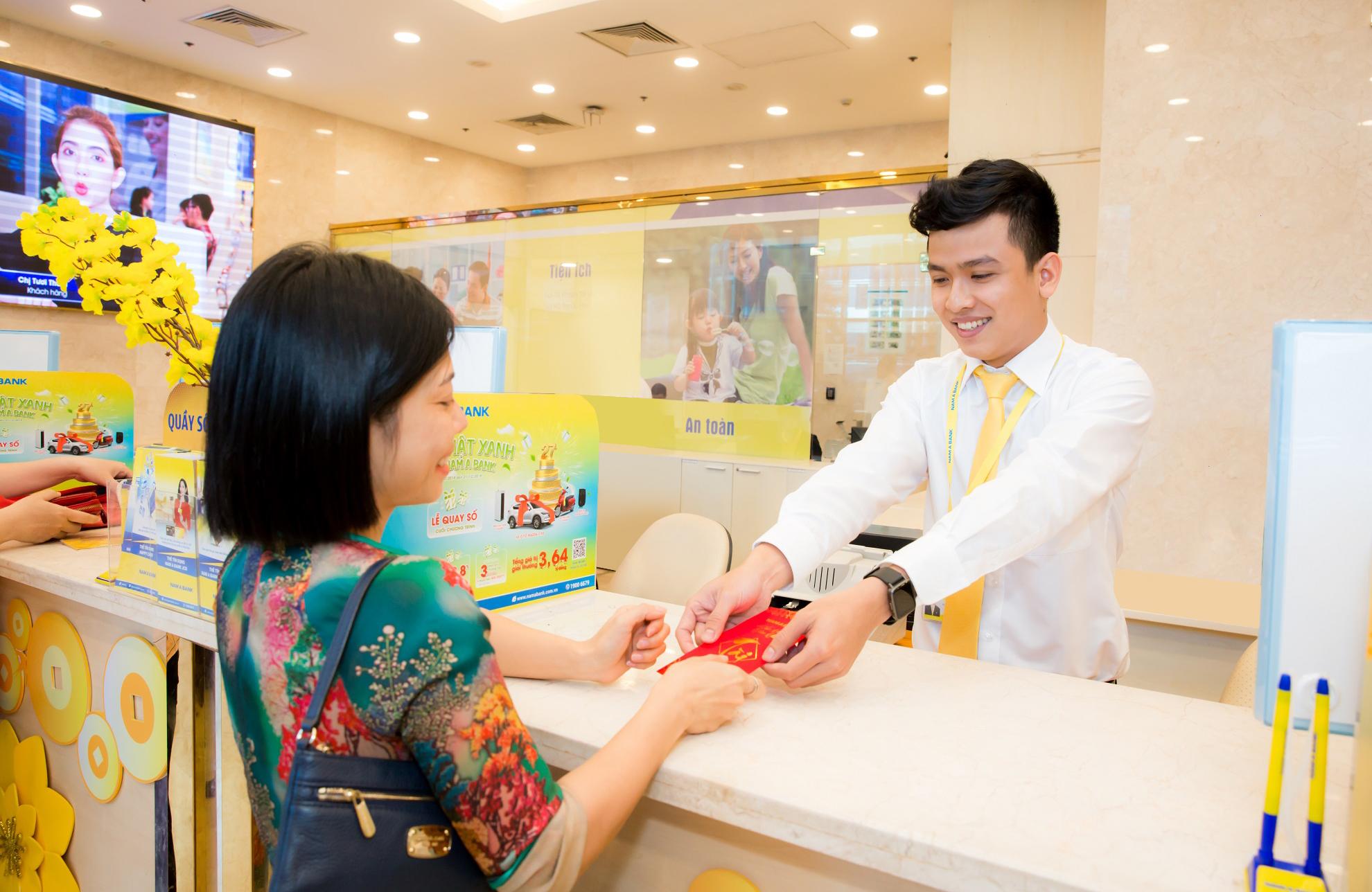 Khách hàng phấn khởi nhận lì xì tại Nam A Bank khi giao dịch đầu năm mới. Nguồn ảnh: Nam Á Bank