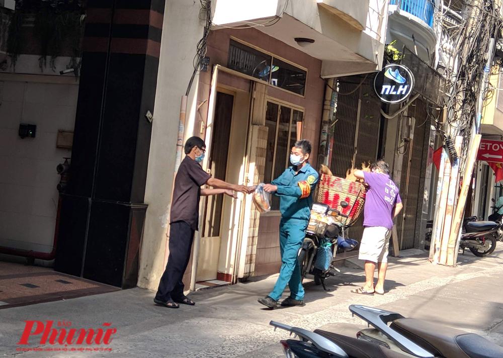 Anh dân quân tự vệ mua bánh mì và chuyển cho những người đang cách ly