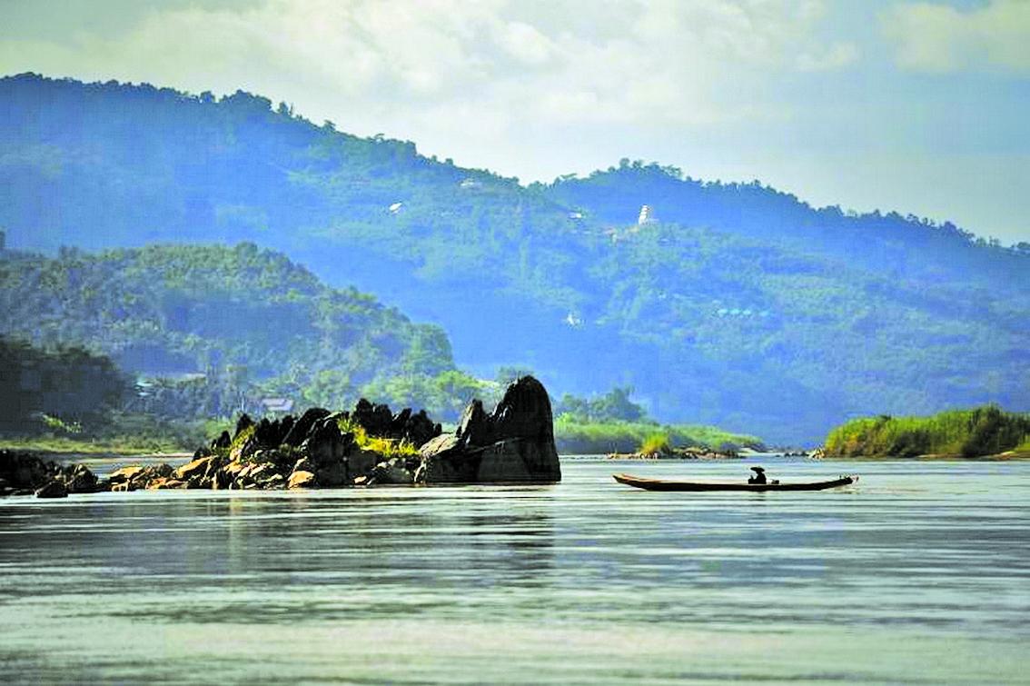 Một ngư dân đi thuyền dọc theo sông Mê Kông, đoạn giữa Thái Lan và Lào, gần Chiang Rai - Ảnh: AFP