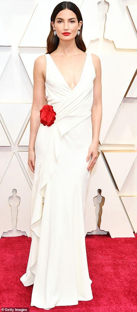 Theo Daily mail, người mẫu nổi tiếng của Victoria's Secret Luly Aldridge trông giống như một ngôi sao điện ảnh lỗi thời trên thảm đỏ khi diện chiếc váy màu trắng kết hợp với bông hoa đỏ ở phần eo.