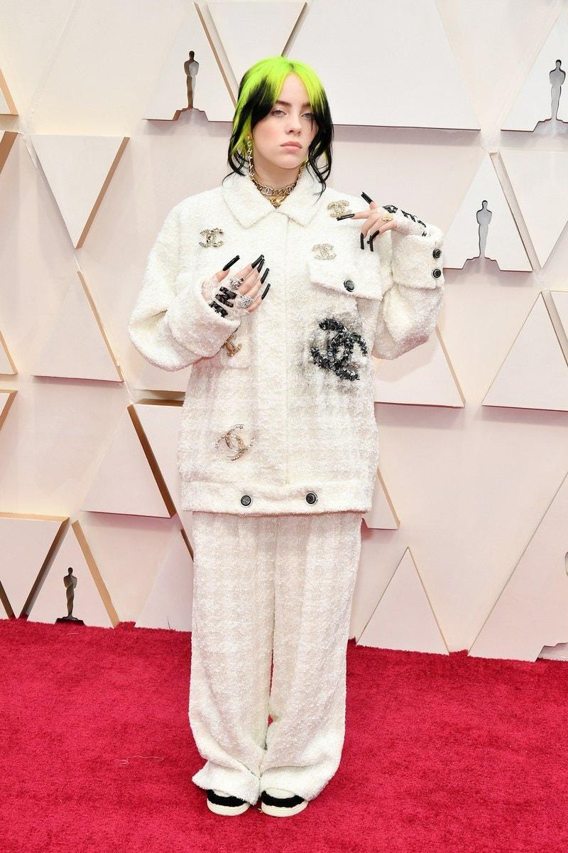 Billie Eilish thể hiện gu thời trang chất lừ của mình trong trang phục Chanel. Trang phục trắng nguyên set giúp mix cùng găng tay, trâm cài áo cùng mái tóc xanh neon giúp nữ ca sĩ 18 tuổi thu hút truyền thông. Mới đây, Billie Eilish đã lập nên kỷ lục nữ ca sĩ trẻ tuổi nhất nhận được cùng lúc 4 giải thưởng quan trọng nhất của Grammy sau Christopher Cross năm 1981.