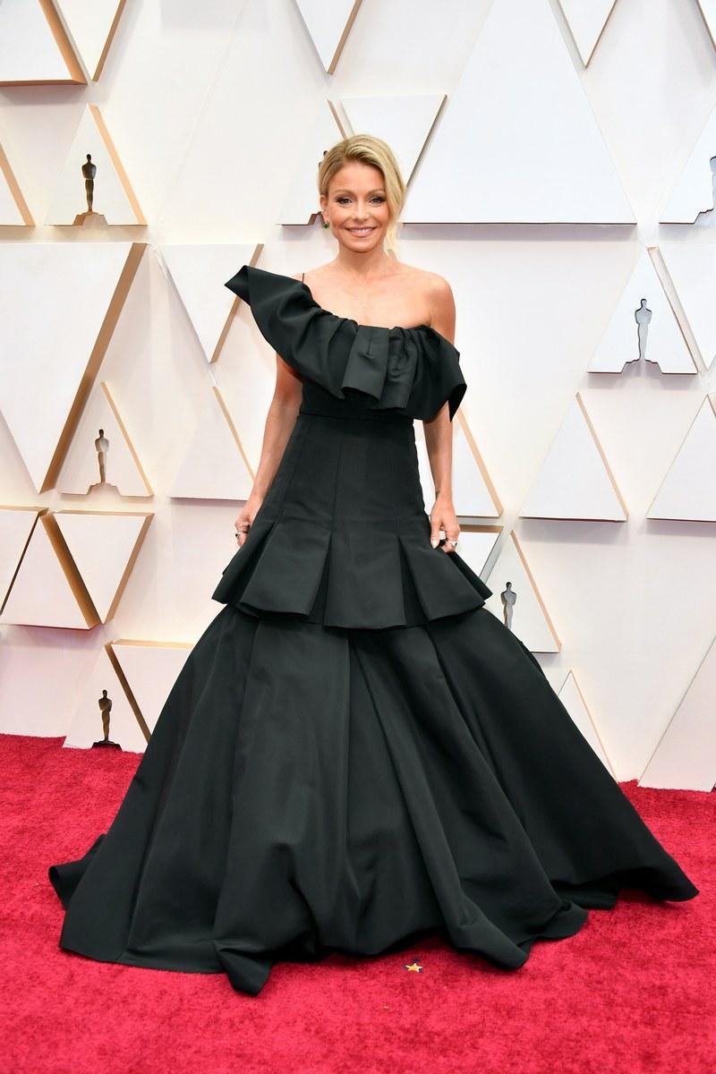 Kelly Ripa quyến rũ trong bộ váy đen bất đối xứng. Thiết kế ôm sát khoe vòng eo nhỏ nhắn và độ phồng ở phần đuôi váy giúp nữ MC thuận tiện trong việc di chuyển.