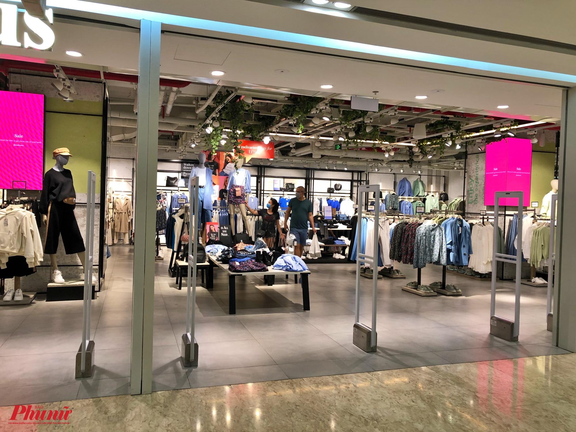 Lầu 2 của trung tâm thương mại Vincom cũng lát đát một vài khách mua sắm, trong ảnh một cặp du khách người nước ngoài đeo khẩu trang chọn mua quần áo ở lầu 2