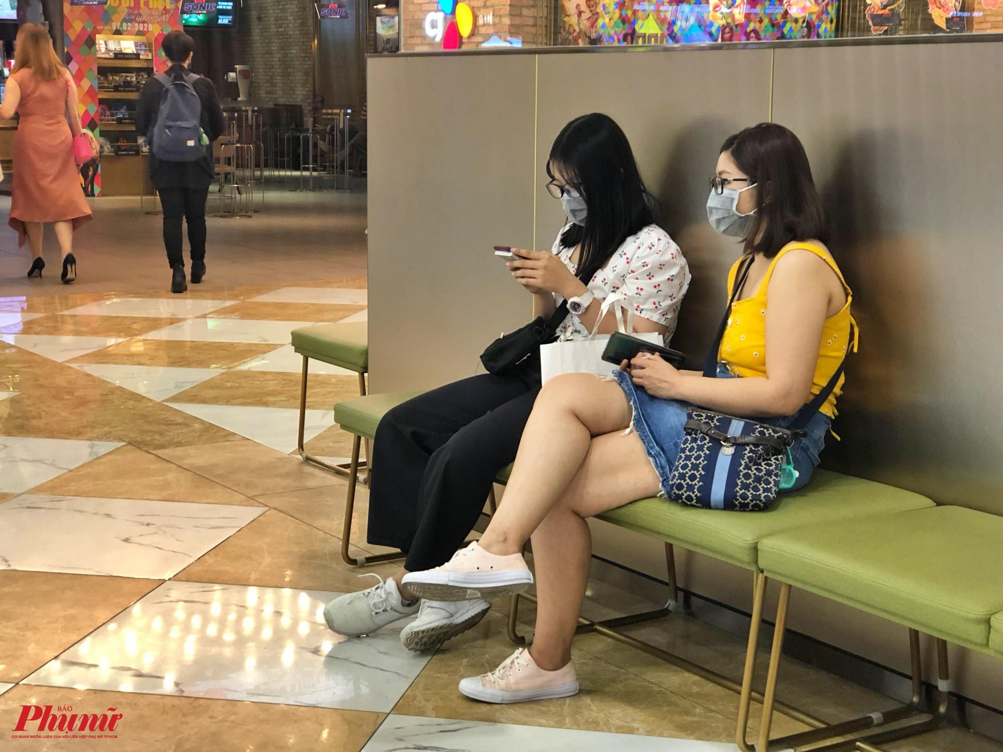 Hai bạn trẻ ngồi đợi trước rạp chiếu phim ở trung tâm thương mại Vincom cũng bịt kín khẩu trang để phòng ngừa sự lây lan của dịch bệnh do virus Corona