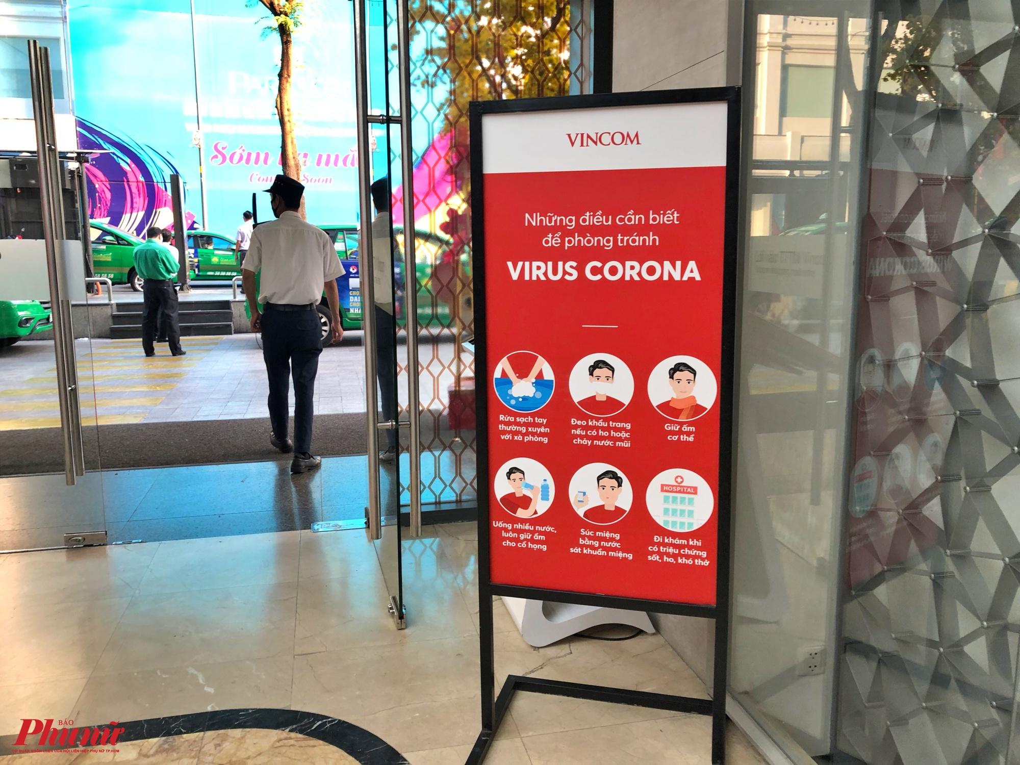 Tại cổng ra vào của trung tâm thương mại Vincom trên đường Lê Thánh Tôn, quận 1 cũng treo bảng cảnh báo cho người dân về cách phòng trách virus Corona như đeo khẩu trang, rửa tay thường xuyên bằng xà phòng