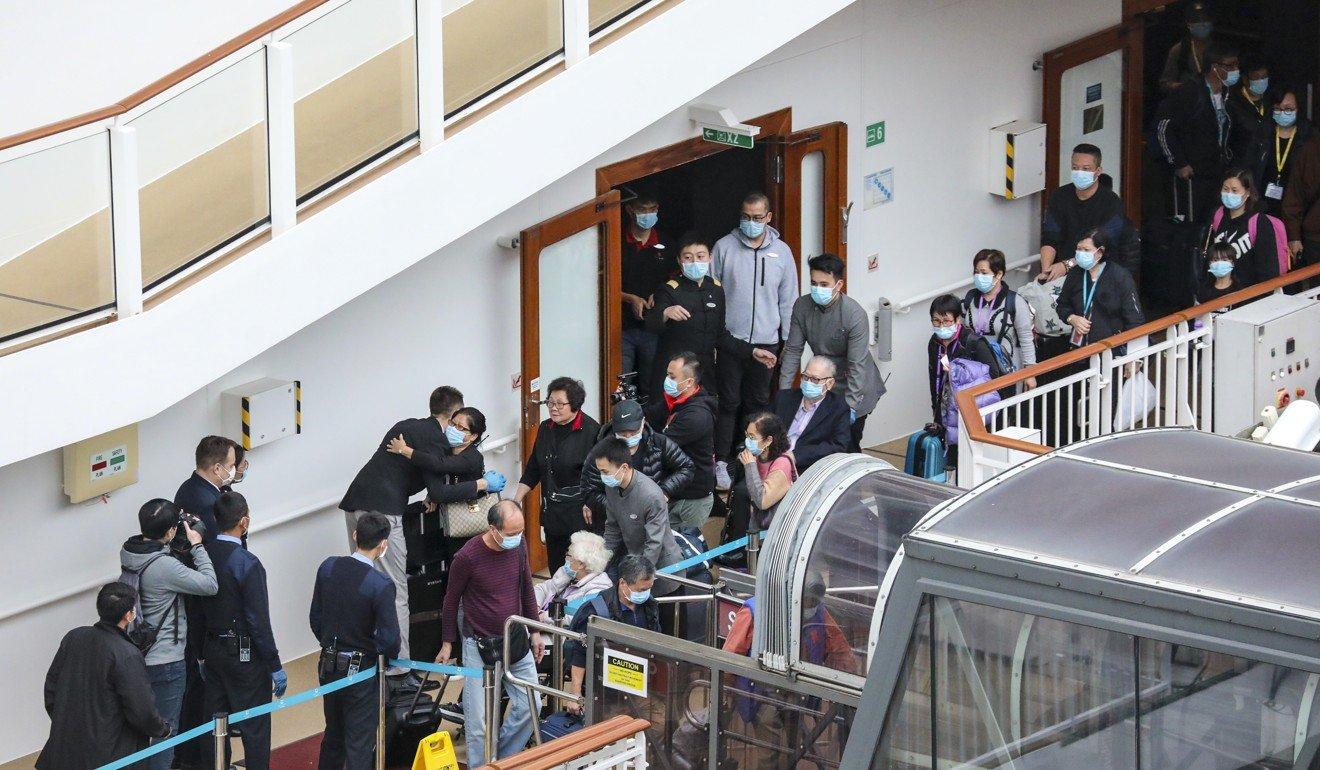 Hành khách xếp hàng rời tàu World Dream hôm 9/2 sau khi bị cách ly - Ảnh: Felix Wong