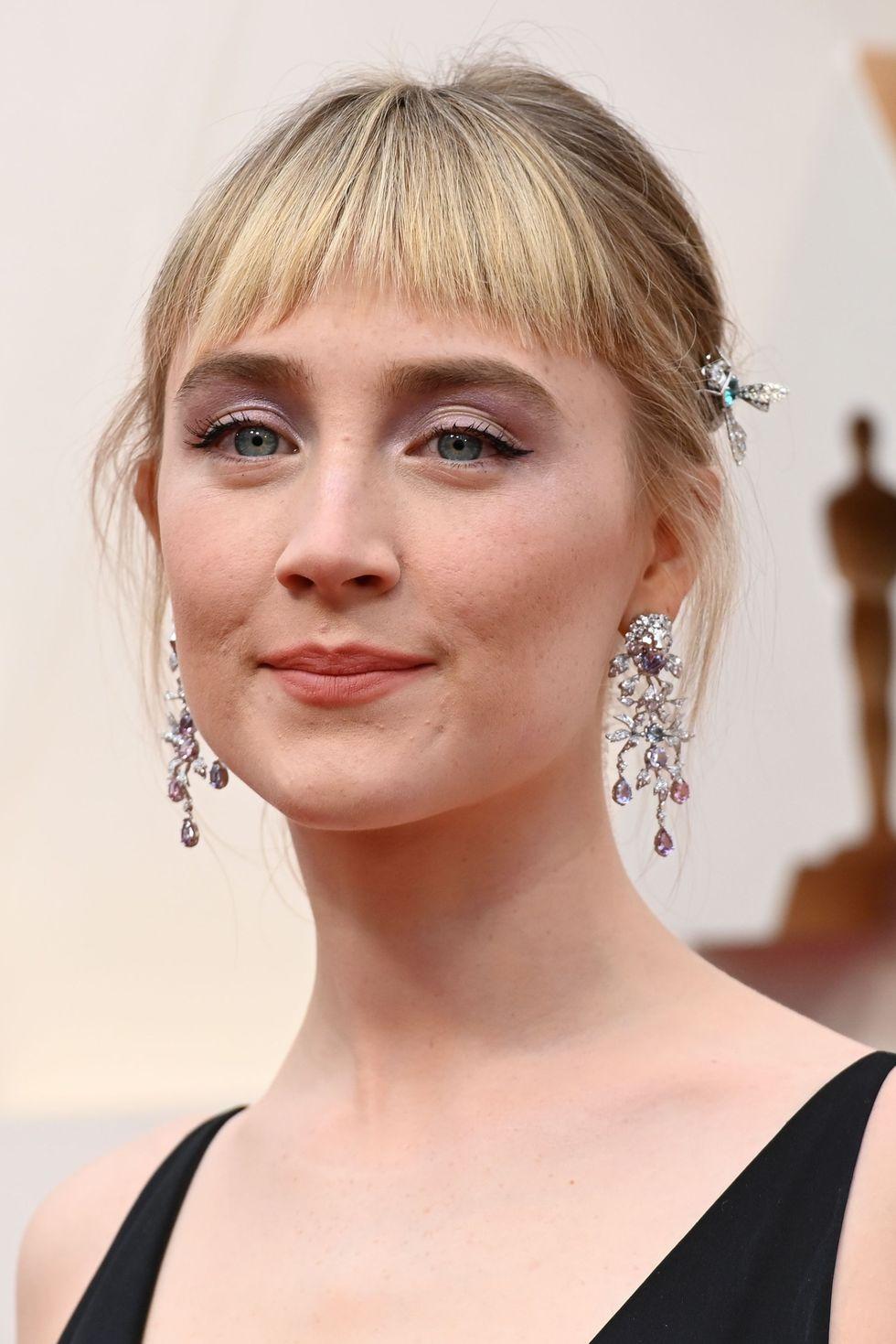 Saoirse Ronan đẹp mọi góc nhìn. Mái tóc nhuộm vàng tươi tắn cho đến kẹp tóc hình bướm, phần mắt ánh tím tạo nên tổng thể khuôn mặt hài hòa.