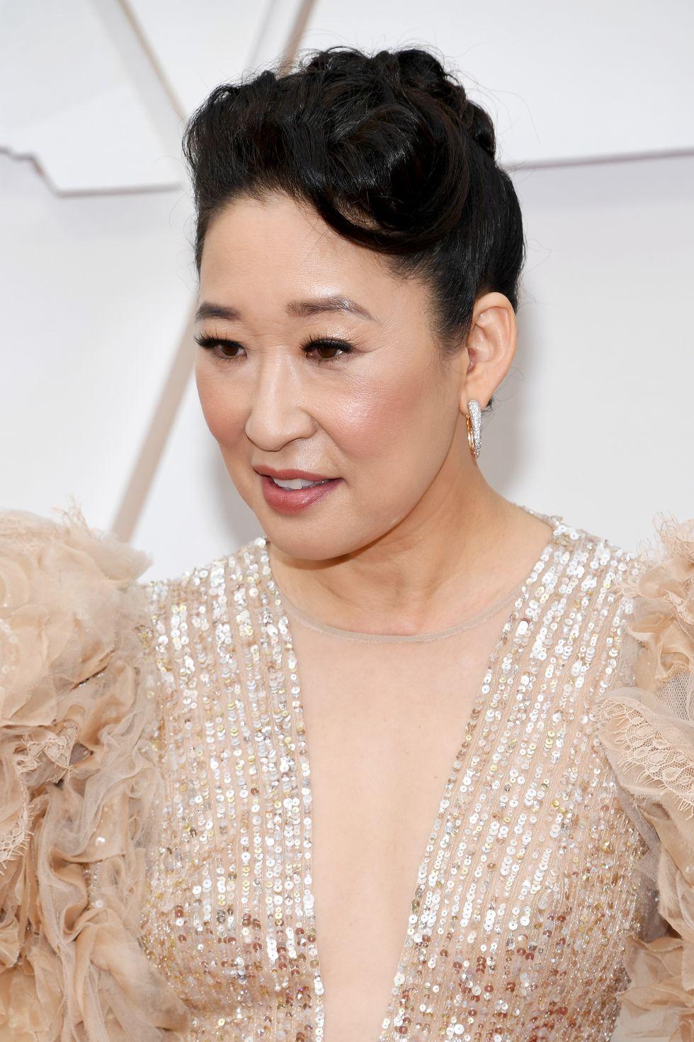 Sandra Oh sang trọng và đẳng cấp với sự giúp đỡ của chuyên gia làm tóc Peter Butler. Phần mái uốn xoăn bồng bềnh phù hợp với bộ cánh cổ điển của nữ diễn viên.
