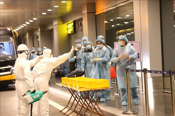 Công dân Việt Nam được hướng dẫn tẩy trùng trước khi làm thủ tục nhập cảnh tại sân bay Vân Đồn. Ảnh: TTXVN