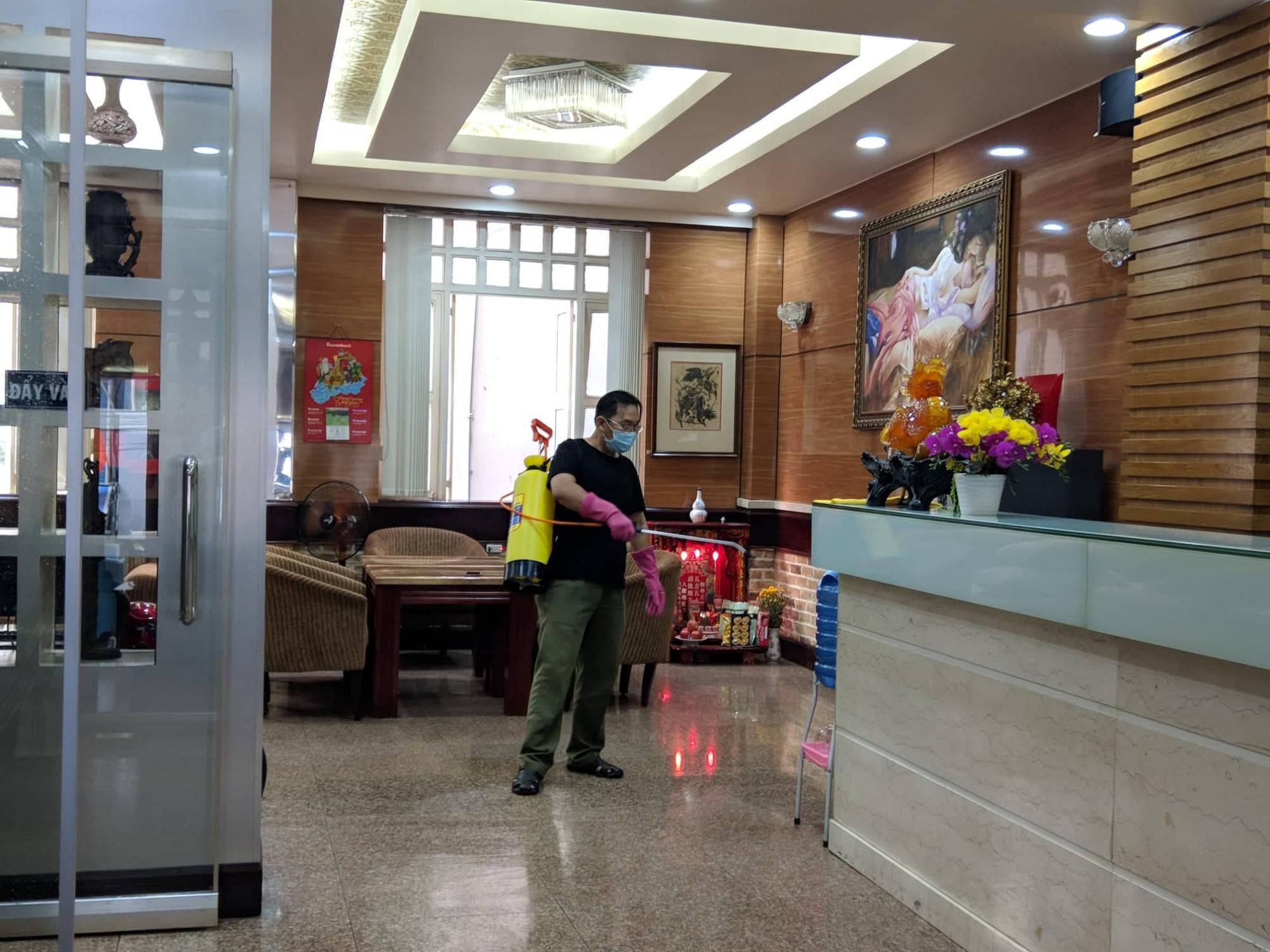 Những nhân viên của khách sạn Triều Hân, nơi có 18 người đang cách ly tập trung phun hóa chất khử khuẩn bên trong khách sạn. Ảnh: Hiếu Nguyễn
