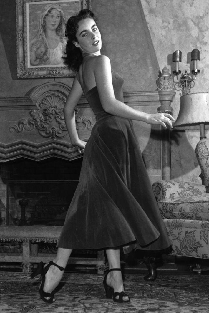 Elizabeth Taylor, tháng 1 năm 1950 Váy đầy đủ và bó sát của váy Elizabeth Taylor là mẫu mực của phong cách trong những năm 1950, nhưng thay vì đi theo xu hướng in và họa tiết tươi sáng của thời đại, ngôi sao trẻ chọn cho mình một loại vải đen đơn giản.