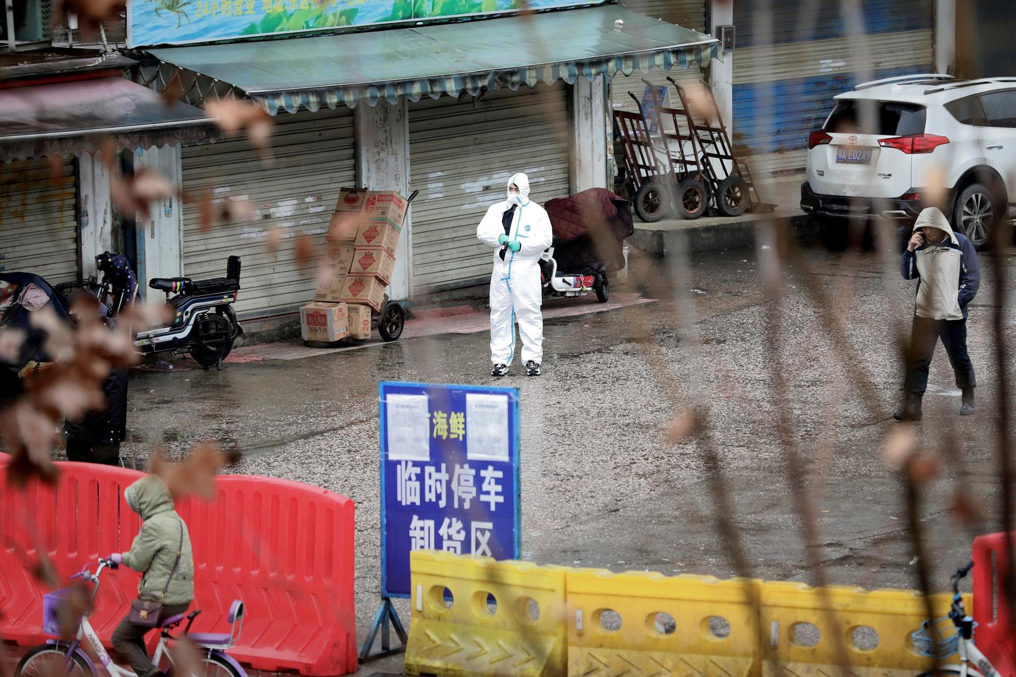 Một công nhân mặc đồ bảo hộ tại một chợ hải sản ở Vũ Hán. Ảnh: Reuters