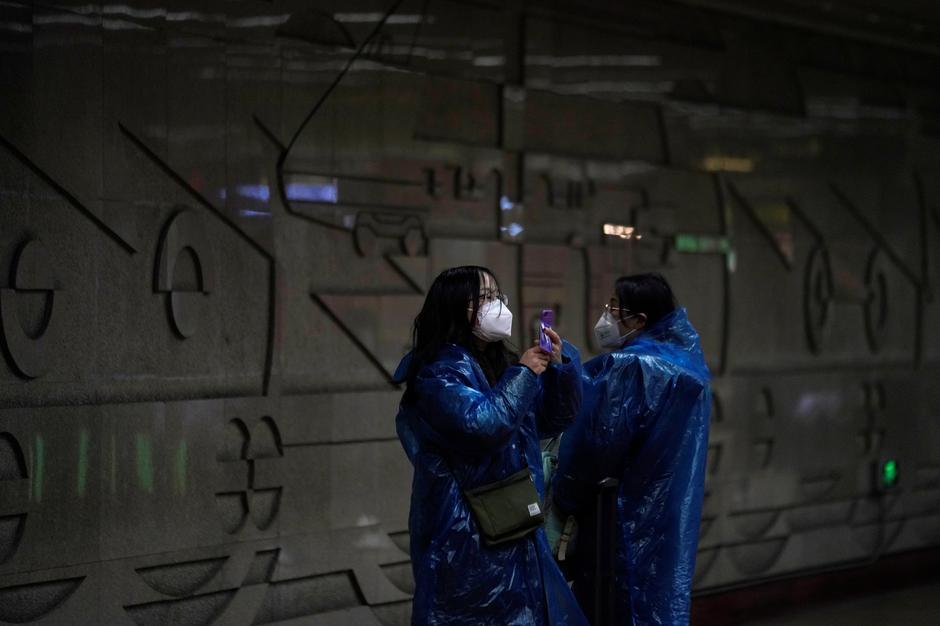 Hình ảnh hành khách mặc áo mưa và đeo khẩu trang tại ga tàu điện ngầm ở Thượng Hải, Trung Quốc - Ảnh: Reuters