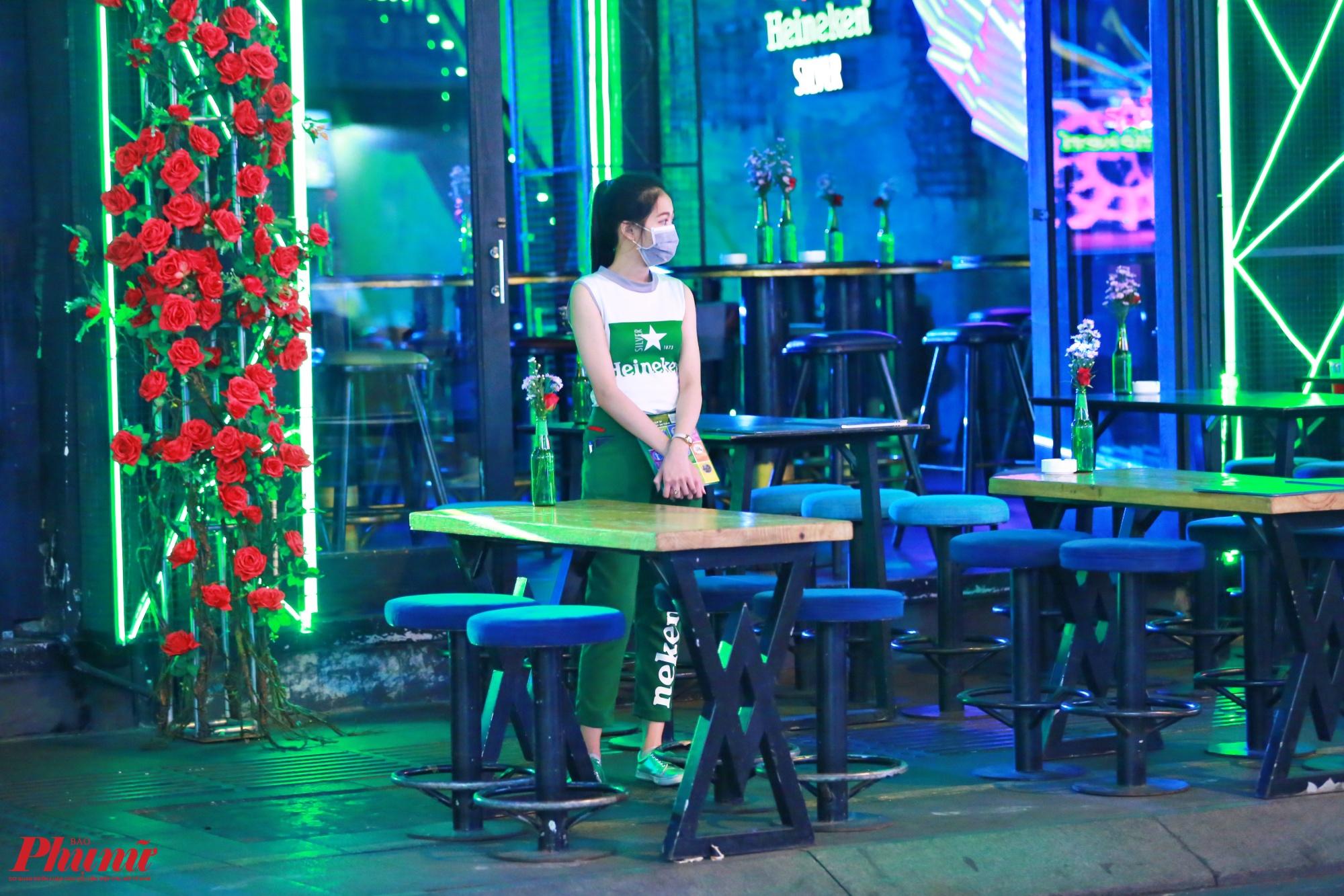 Một nhân viên phục vụ quán bar bịt khẩu khẩu, đứng một mình đợi khách