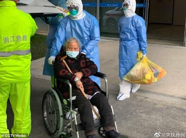 Các nhân viên y tế trong bộ đồ bảo hộ giúp đưa bà Lu lên xe để về điều trị tiếp các bệnh khác tại địa phương.
