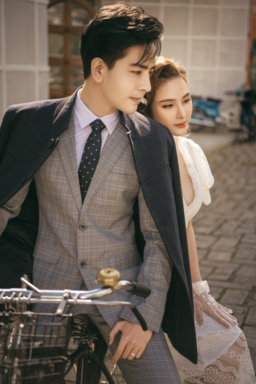 Cả hai chọn phong cách thời trang cổ điển với bộ vest sọc caro sang trọng và bộ váy ren quyến rũ với phần cổ khoét sâu gợi cảm.