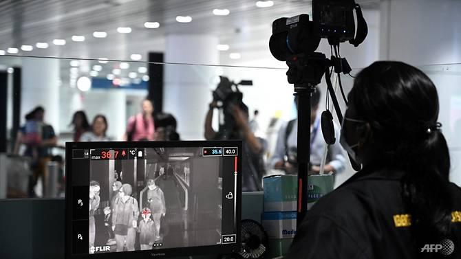Một nhân viên y tế Malaysia sàng lọc hành khách đến bằng máy quét nhiệt tại sân bay quốc tế Kuala Lumpur.