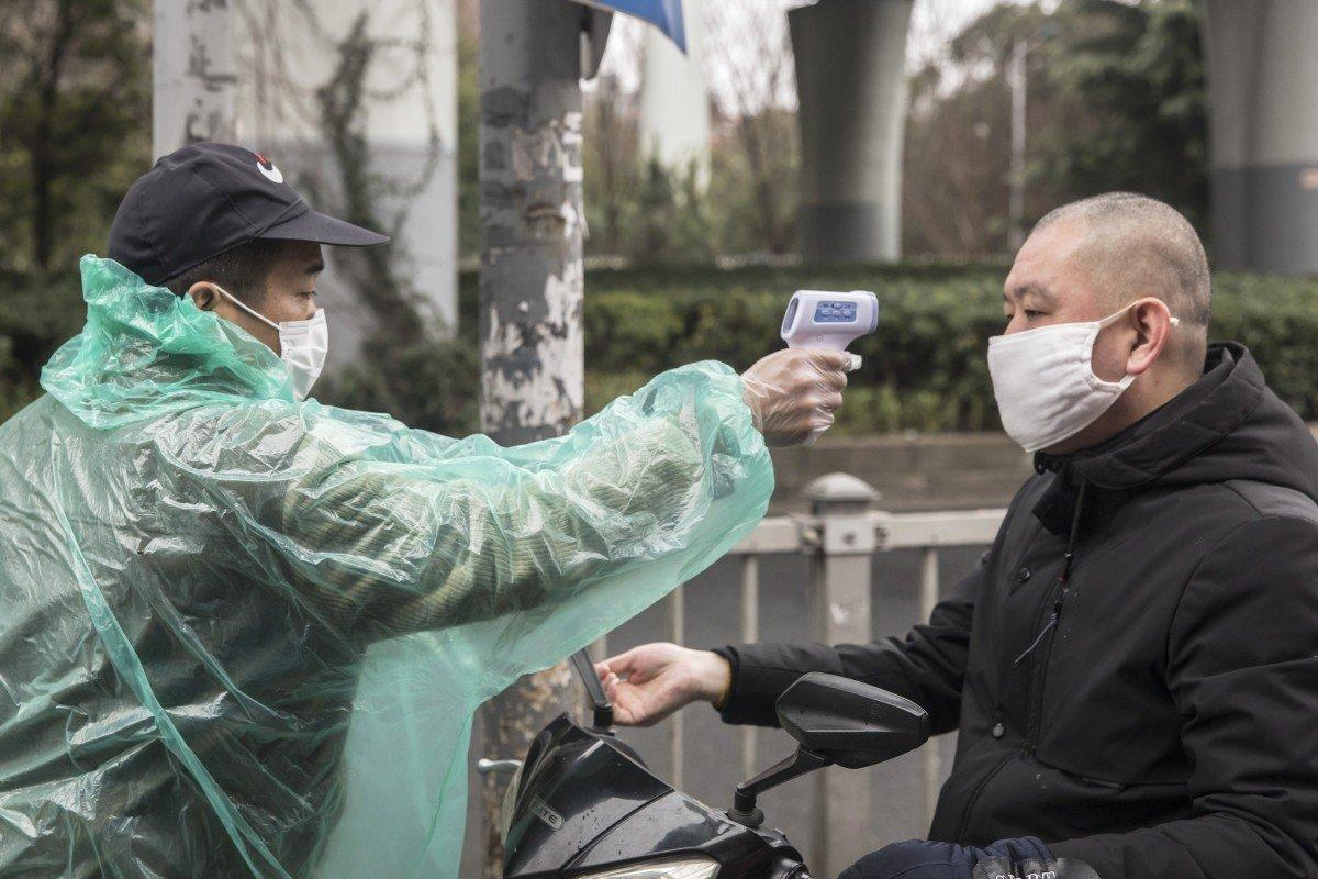 Một nhân viên bảo vệ kiểm tra thân nhiệt của một người đàn ông tại một khu chợ ở Thượng Hải - Ảnh: Bloomberg