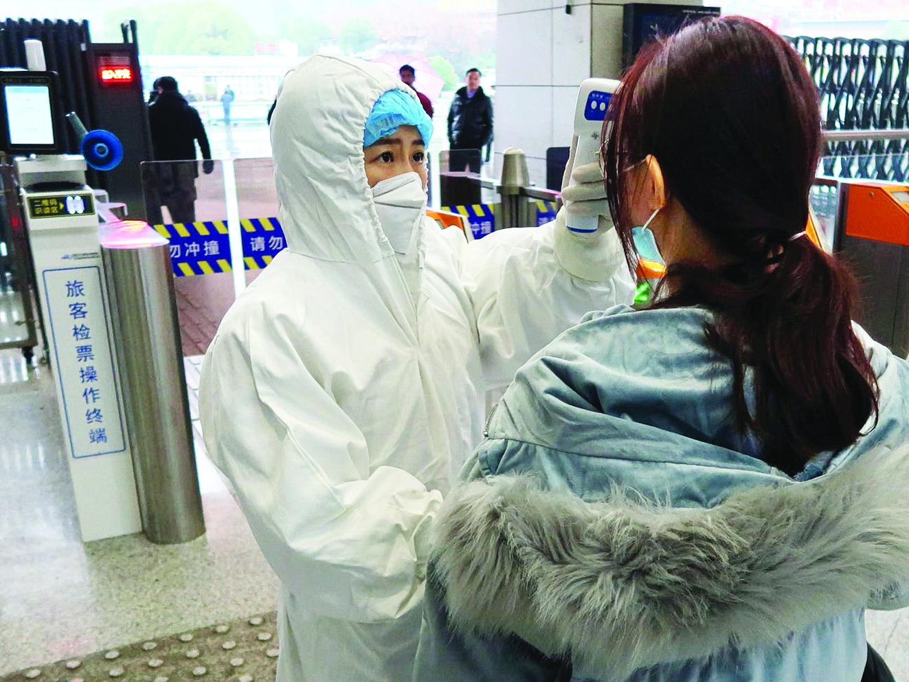 Kiểm tra thân nhiệt hành khách tại một nhà ga Trung Quốc - ẢNH: REUTERS