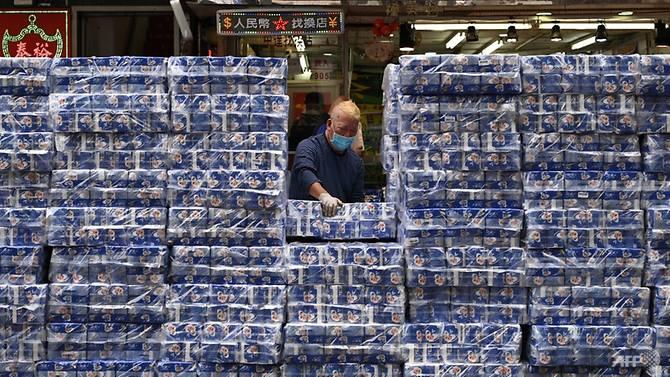 Một người đàn ông đeo khẩu trang sắp xếp các gói giấy vệ sinh được bán tại một cửa hàng ở quận Tsuen Wan của Hồng Kông.