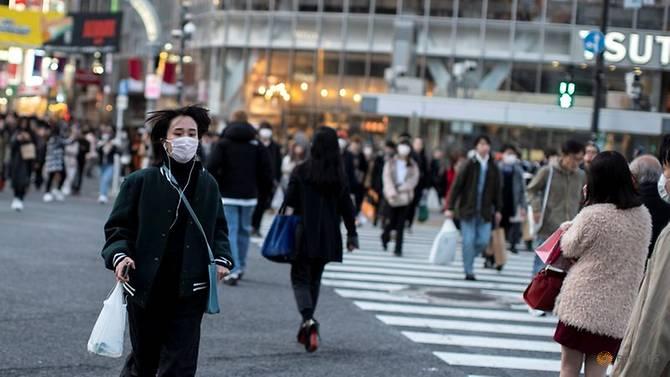 Một người phụ nữ đeo khẩu trang chạy băng qua đường tại khu Shibuya ở Tokyo, vào ngày 17/2.
