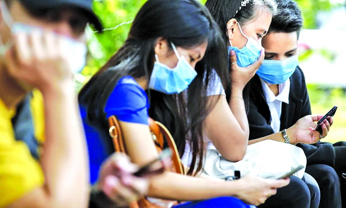 Người lao động từng làm việc ở Hồng Kông bị mắc kẹt lại ở Manila, Philippines, đang ngồi chờ nhận hỗ trợ tài chính từ Bộ Lao động - Ảnh: Geric Cruz (Bloomberg)