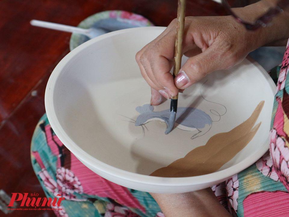 Nghệ nhân gốm thực hiện công đoạn chấm men vẽ hoa văn.