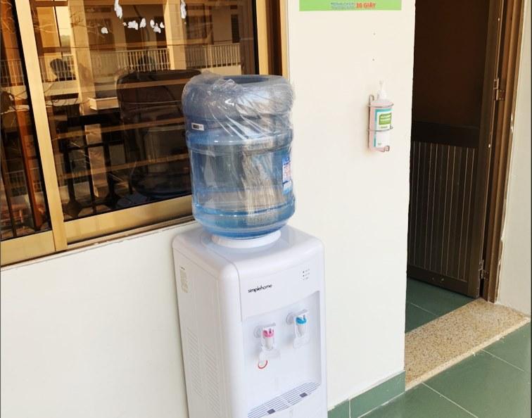 Trước mỗi phòng cách ly đều có bình nước uống nóng - lạnh và bình dung dịch sát trùng tay nhanh.