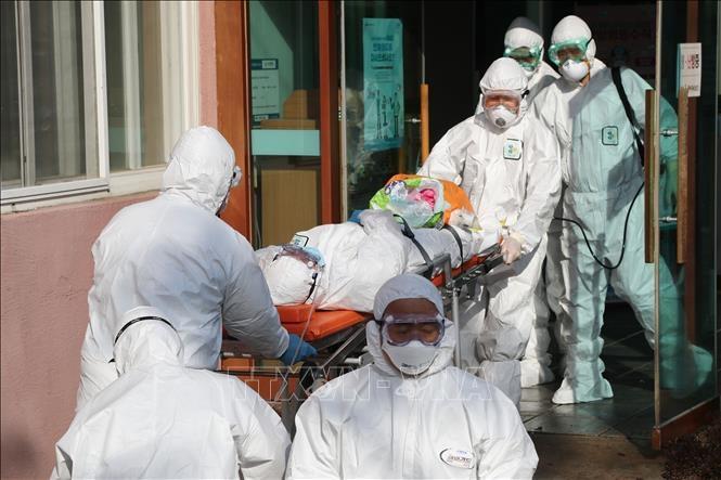 Nhân viên y tế Hàn Quốc chuyển bệnh nhân nhiễm COVID-19 từ một bệnh viện ở Cheongdo đến một bệnh viện khác để điều trị ngày 21/2/2020 (Ảnh: Yonhap/TTXVN)
