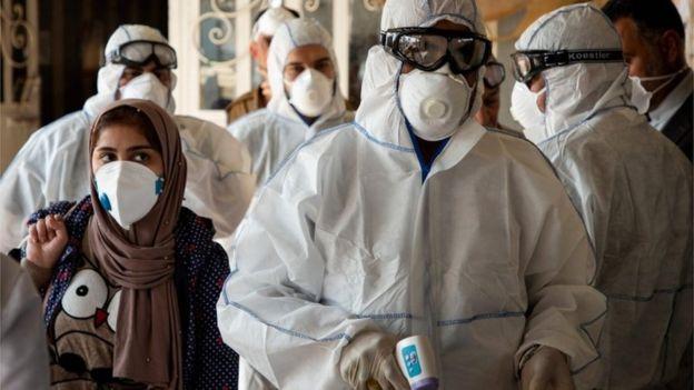 COVID-19 bắt đầu phủ bóng đen lên các quốc gia vùng Trung Đông. Trong ảnh là các nhân viên y tế Iraq kiểm tra thân nhiệt hành khách đến từ Iran.
