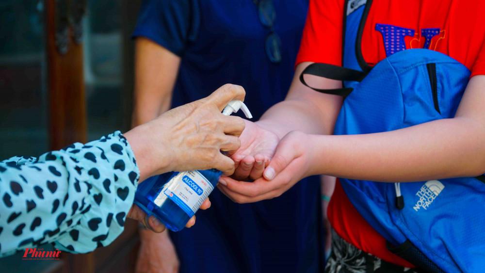 Xịt dung dịch rửa tay diệt khuẩn cho người dân trước khi vào Lễ