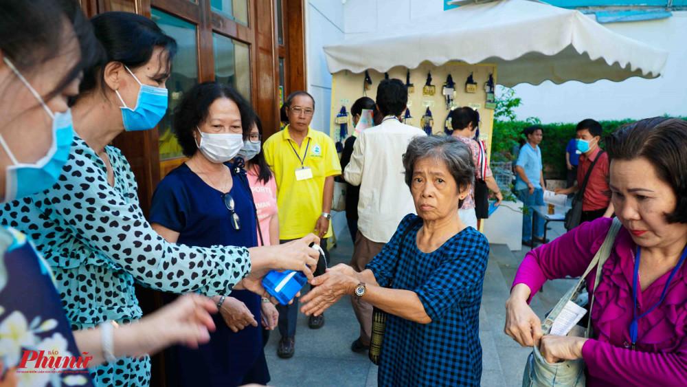 Người dân xép hàng xịt dung dịch rửa tay diệt khuẩn trước khi vào khu vực làm Lễ