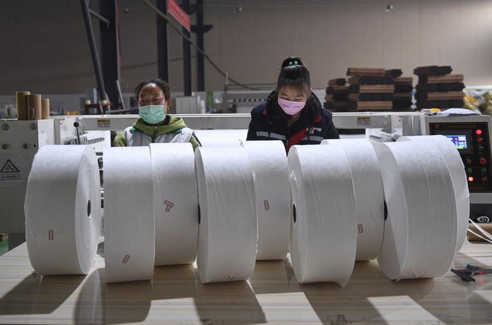 Nhân viên sắp xếp các cuộn vải không dệt tại xưởng của một công ty ở Thành Đô, tỉnh Tứ Xuyên, Trung Quốc. Nhiều nhà máy chuyển sang sản xuất khẩu trang để đáp ứng nhu cầu chống dịch COVID-19 - Ảnh: Tân Hoa Xã