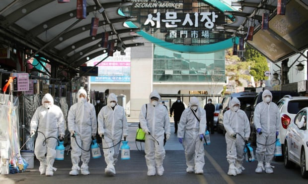 Nhân viên y tế phun thuốc khử trùng một ngôi chợ tại Daegu hôm 23/2.
