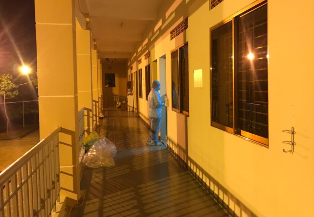 Một nhân viên của kíp trực mặc áo phòng hộ sang khu vực cách ly chuẩn bị phòng cho người cách ly mới sắp tiếp nhận