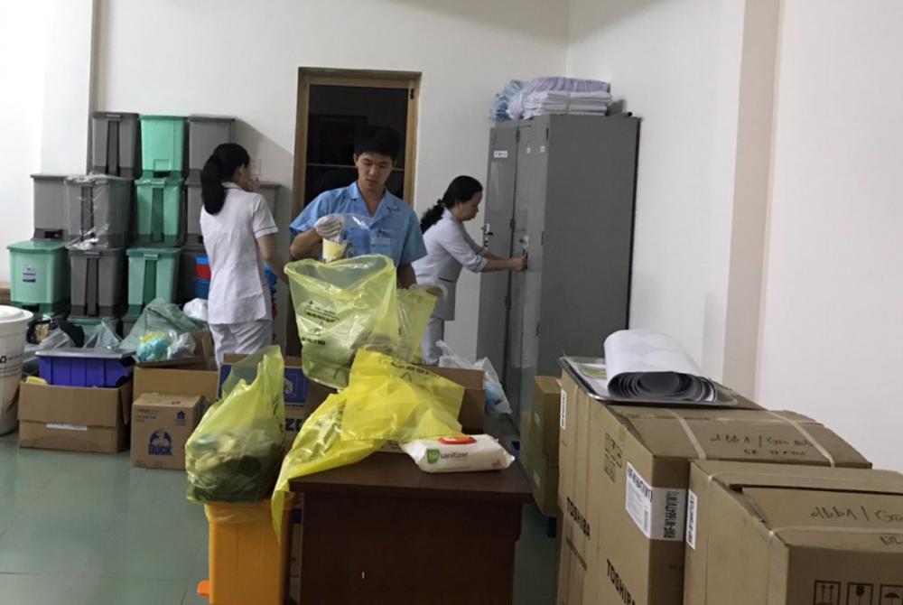 3 nhân viên khác khẩn trương chuẩn bị đồ dùng cá nhân và các tiện ích khác cho người sắp được cách ly tại khu hành chánh của bệnh viện