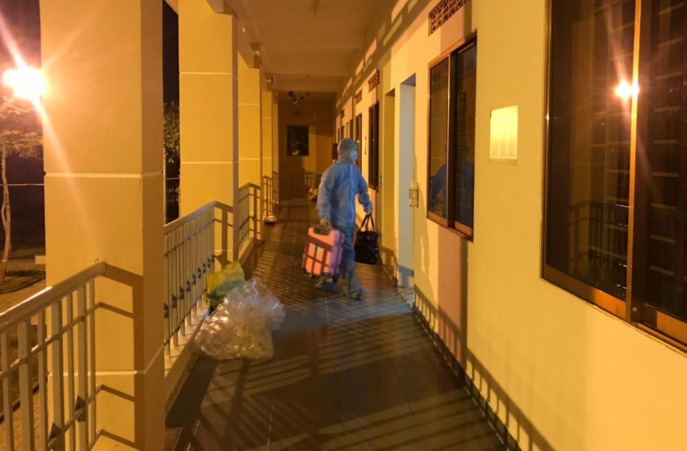 Một nhân viên kíp trực hỗ trợ mang hành lý của người cách ly lên phòng cách ly