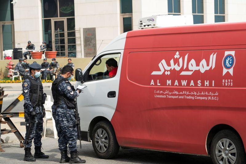 Nhân viên an ninh kiểm tra giấy tờ của một xe tải vận chuyển thiết bị y tế trước khi vào khu vực cách ly tại Kuwait hôm 24/2.