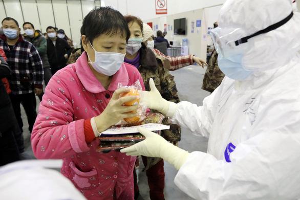 Bệnh nhân đang điều trị nhiễm COVID-19 nhận phần ăn trong bệnh viện dã chiến ở Trung Quốc.