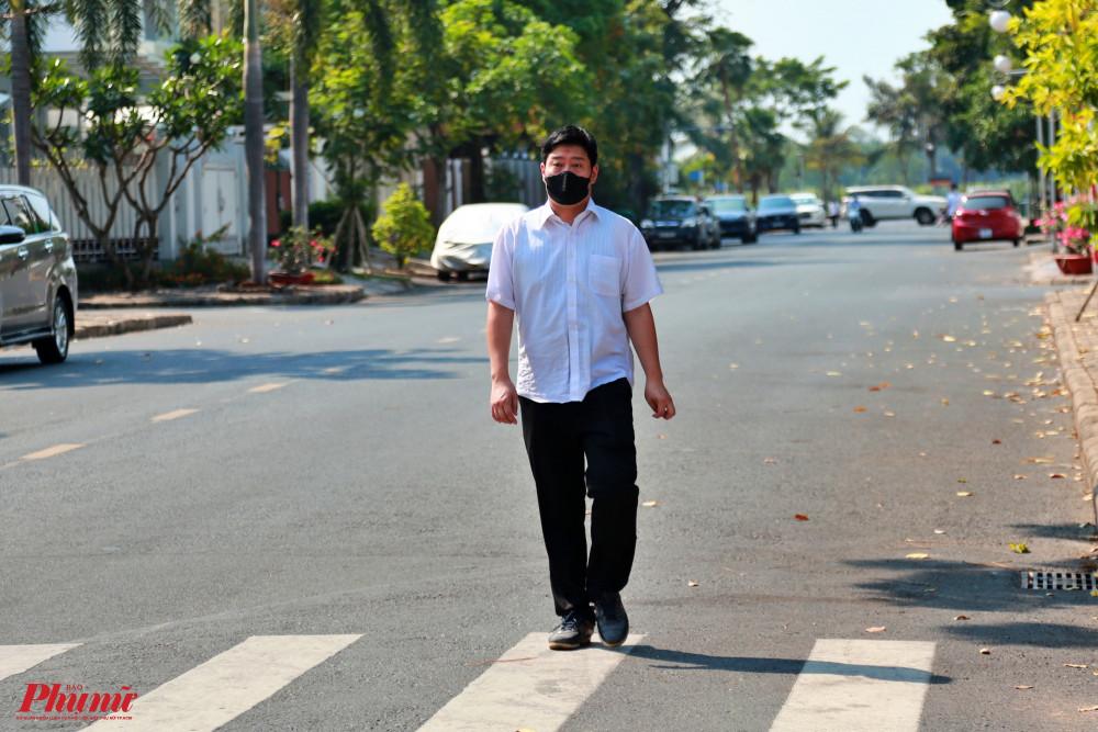 Một người đàn ông Hàn Quốc bịt khẩu trang đi dạo trong khuôn viên khu Mỹ Tú 1 - Phú Mỹ Hưng, quận 7