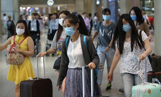 Du khách nước ngoài đeo khẩu trang tại sân bay Hàn Quốc. Ảnh: EPA