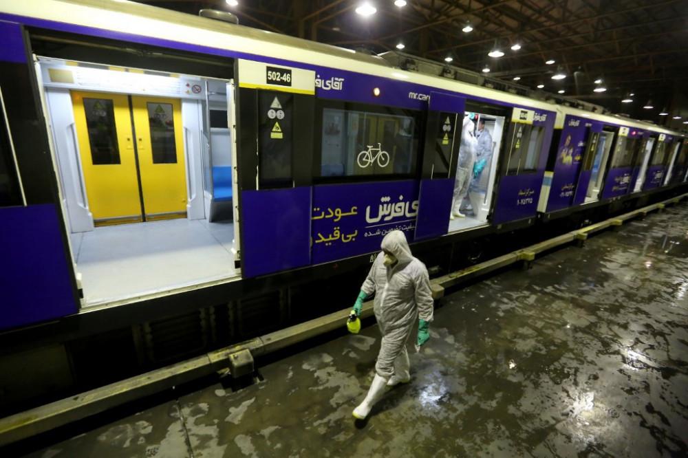 Nhân viên làm vệ sinh một toa tàu ở Tehran để ngăn ngừa COVID-19. Ảnh: AFP